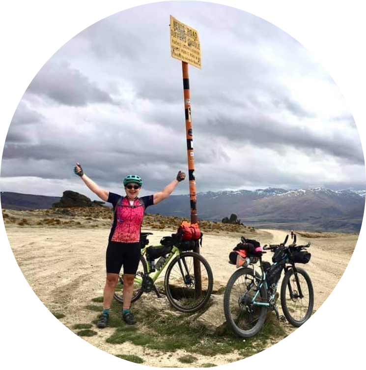female cyclist with arms in the air next to a sign post with two bicycles propped against it